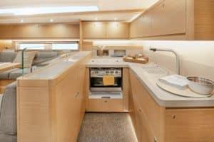 Blick in die Küche des Segelbootes Dufour 530. Zu sehen ist die eine Seite der über die gesamte Breite der Yacht gebauten Küche mit Backofen, Spüle, Kühlschubladen und viel Stauraum. Durch ihre Lage und die komfortable Anordnung lässt sich diese auch bei hartem Seegang gut bedienen.