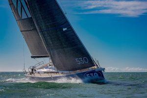 Seitliche Ansicht der Dufour 530 von Vorne, wie sie vor Mallorca unter vollen Segeln durch die Wellen gleitet.