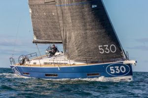 Lateral view of the Dufour 530 from the front, as it glides through the waves under full sail off Mallorca.