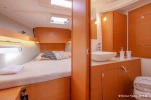 View into the forehead cabin with bath en suite of the Dufour 390 sailboat in oak wood. There is a lot of space and natural light to find comfort and relax.