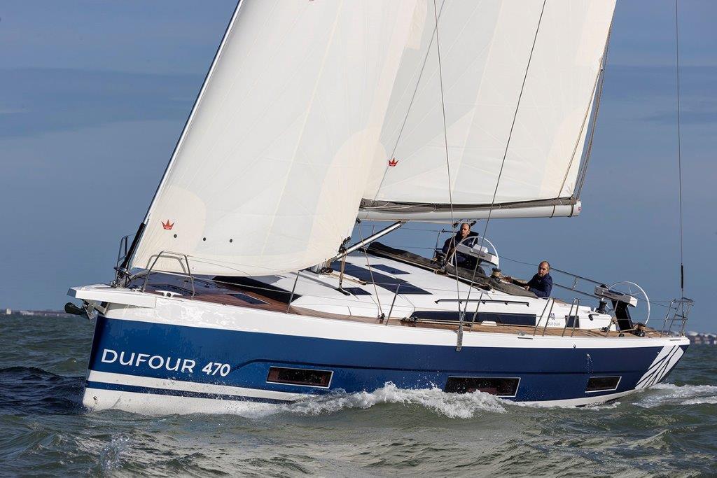 Seitliche Ansicht der Segelyacht Dufour 470 von Vorne, wie sie vor Mallorca unter vollen Segeln durch die Wellen gleitet.