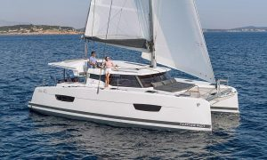 Side view of the Fountaine Pajot sailing catamaran Isla 40 as it glides through the waves under full sail off the coast of Mallorca