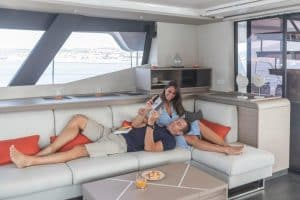 The modern and comfortable sofa and lounge area in the salon of the Fountaine Pajot Samana 59 catamaran offers plenty of space to sit, lie down, relax