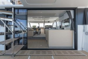 The large sliding glass doors of the Fountaine Pajot MY6 open the salon across the entire width to the seating area of the stern cockpit outside.